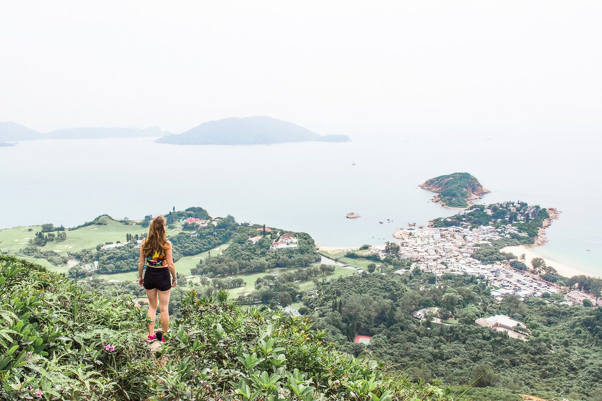 Woman standing on viewpoint overlooking a bay in Hong Kong.