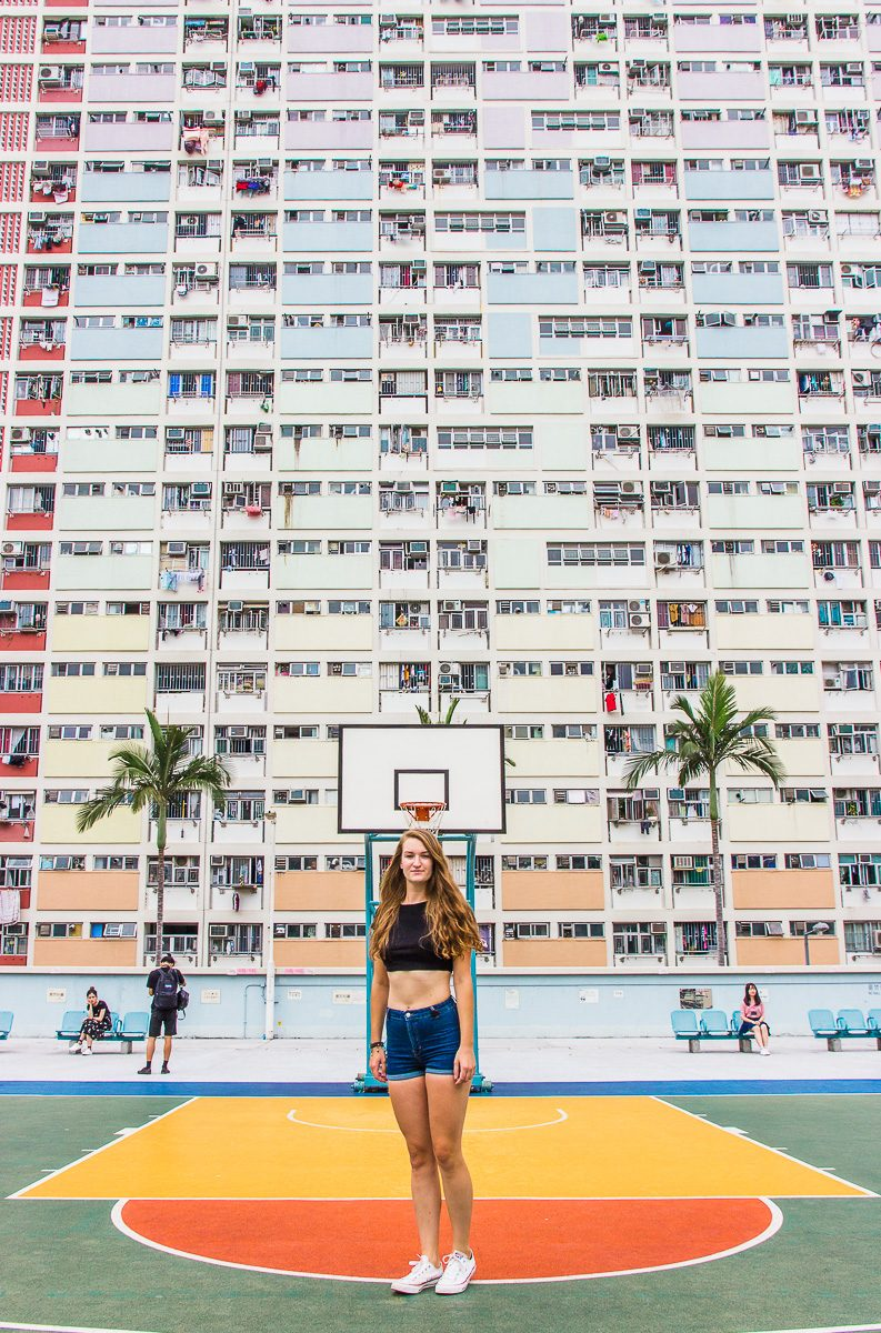 Choi Hung Estate in Hong Kong. Woman standing on colourful basketball court in front of a rainbow colored building in Hong Kong.