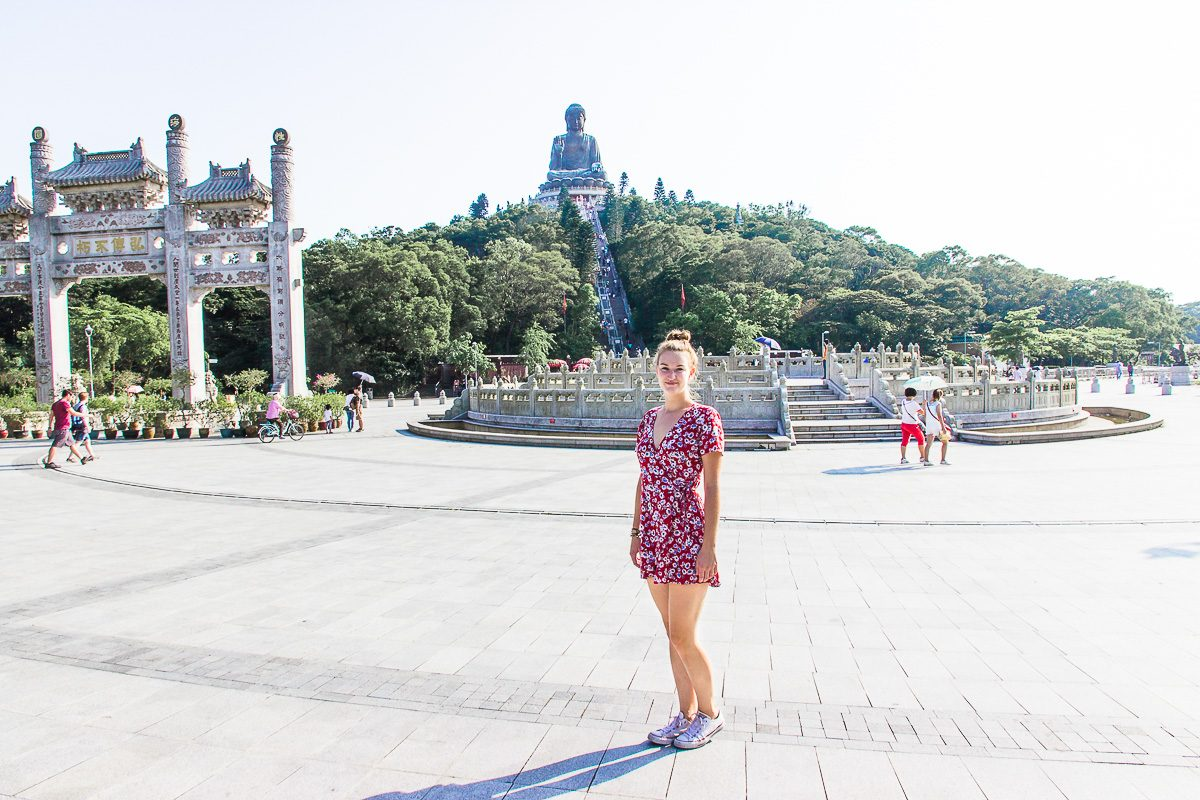 Woman standing in front of the Big Buddha in Hong Kong.