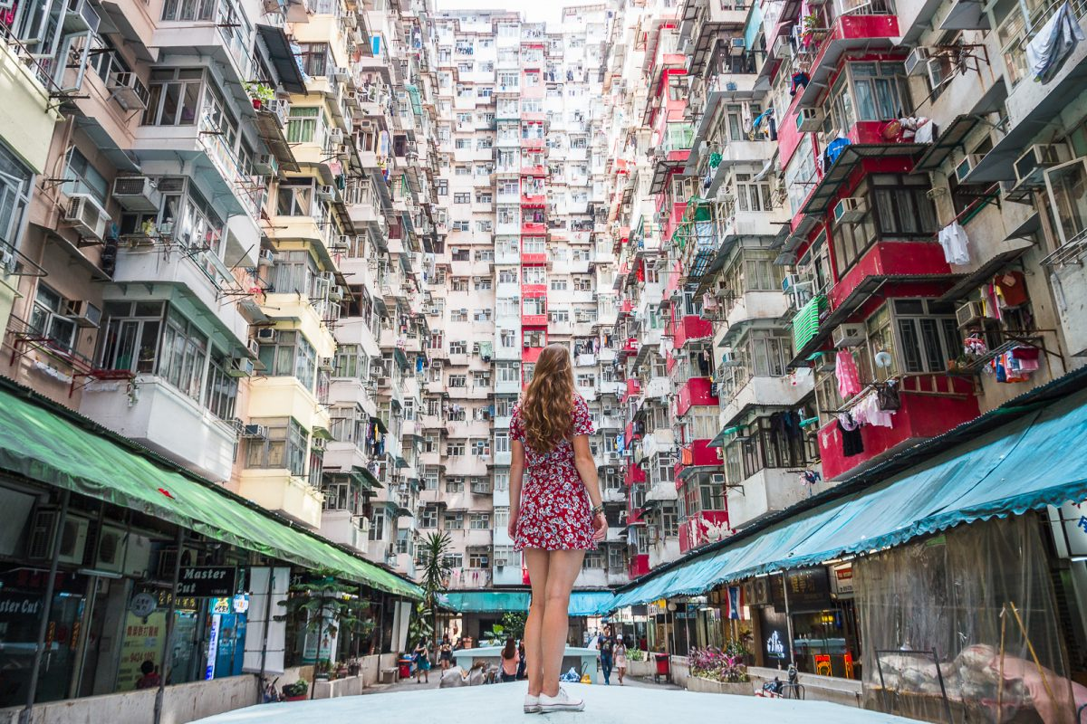 Woman standing on top of platform surrounded by apartment buildings on three sides.
