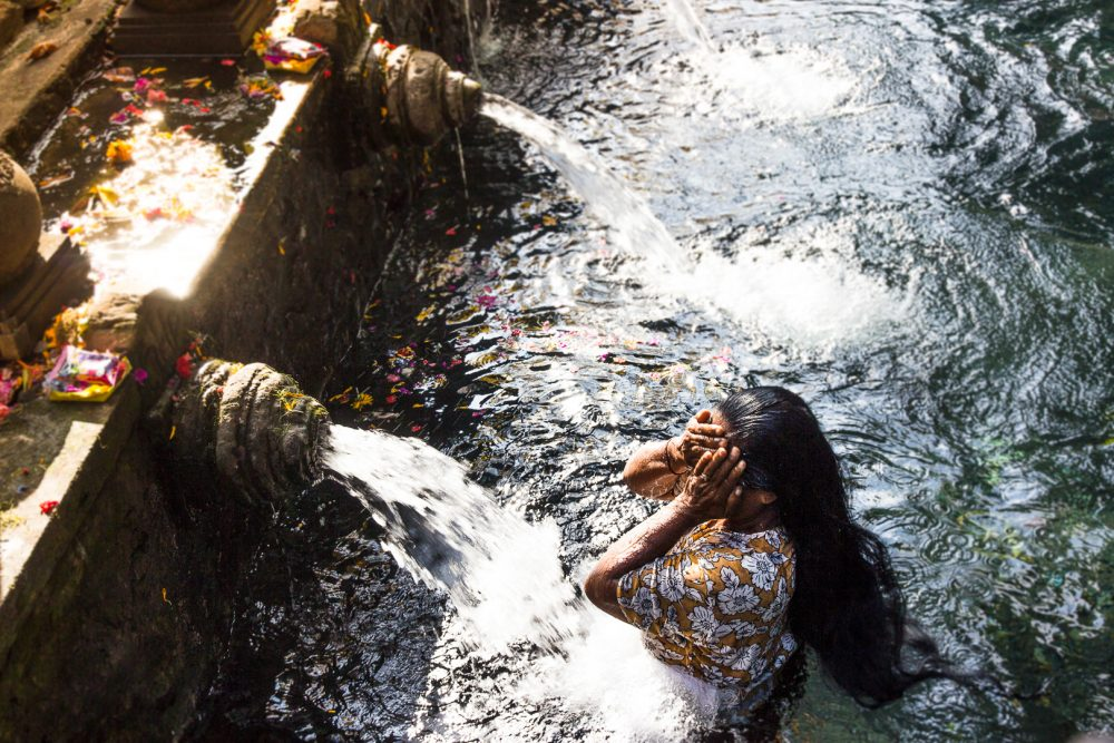 Woman participating in the purification ritual at the Tirta Empul Temple in Bali