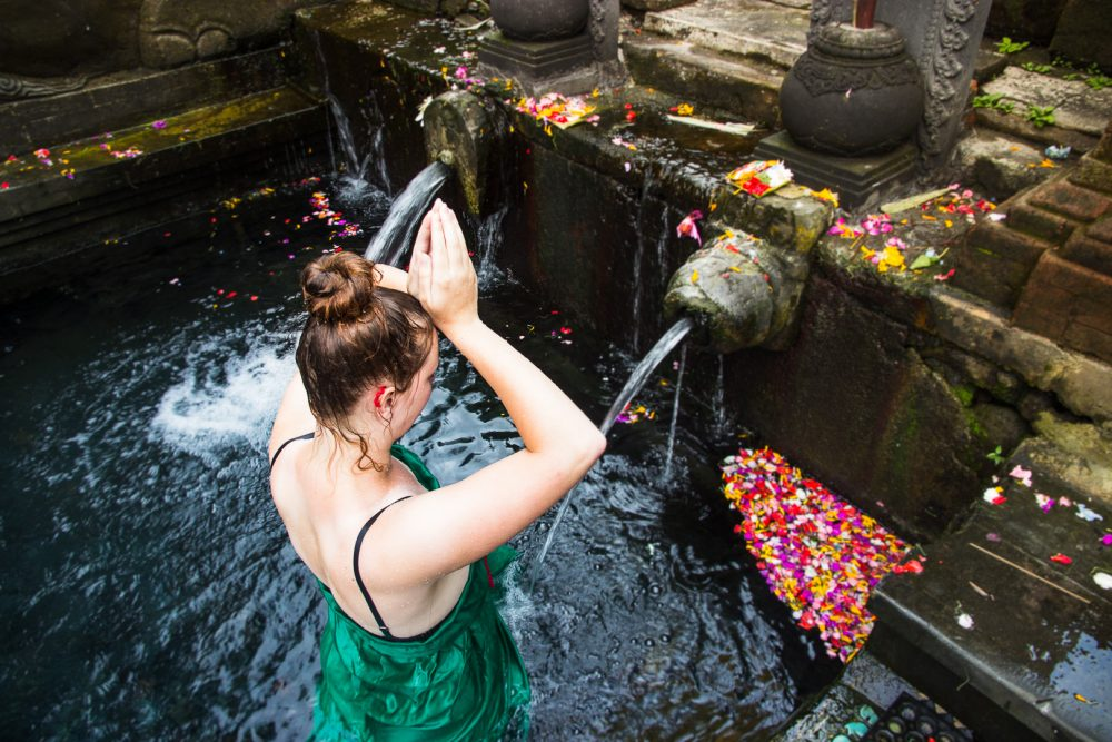 Woman participating in the purification ritual at the Tirta Empul Temple