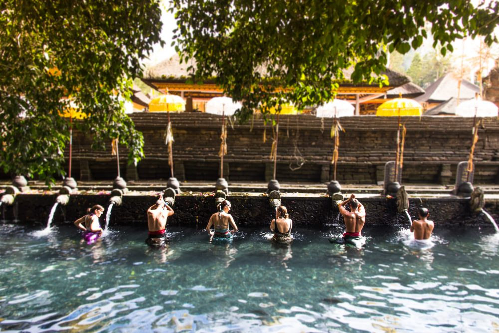 People participating in the purification ritual at the Tirta Empul Temple in Bali