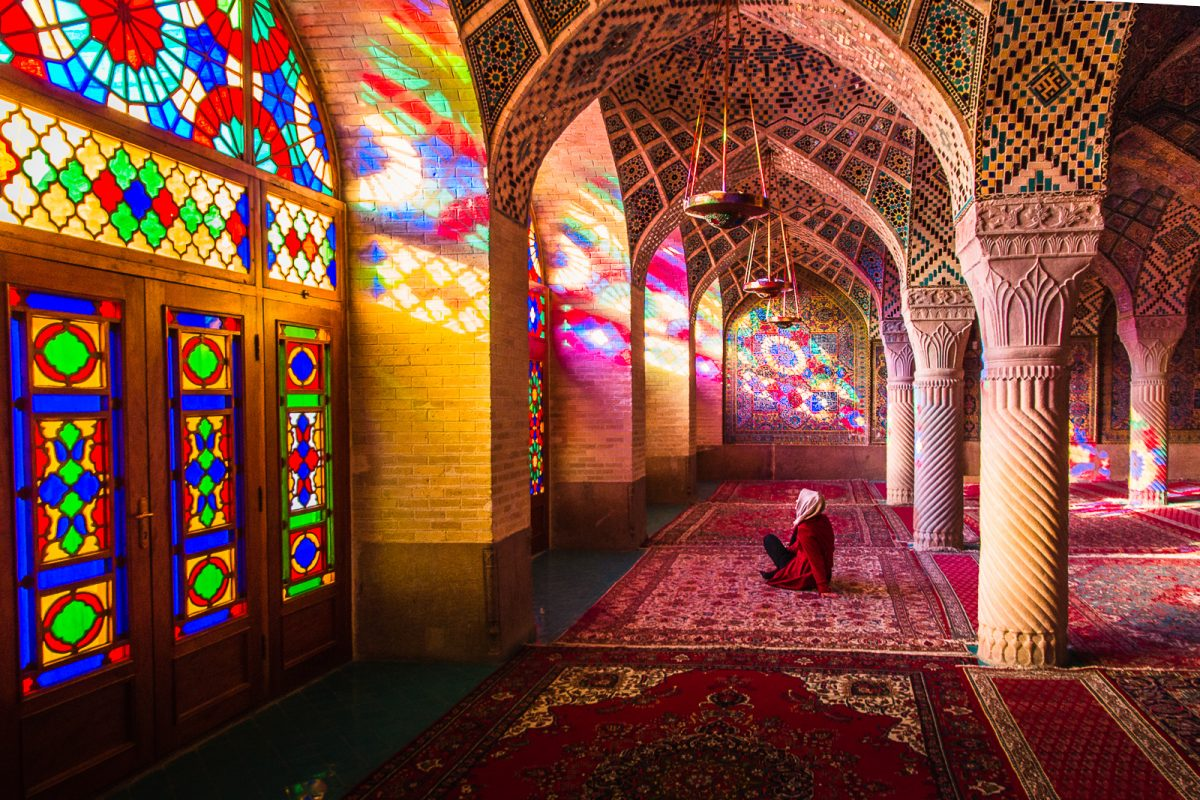 woman sitting in the nasir al mulk mosque in iran