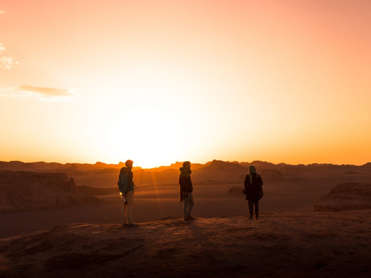 People watching sunrise in the Lut Desert in Iran