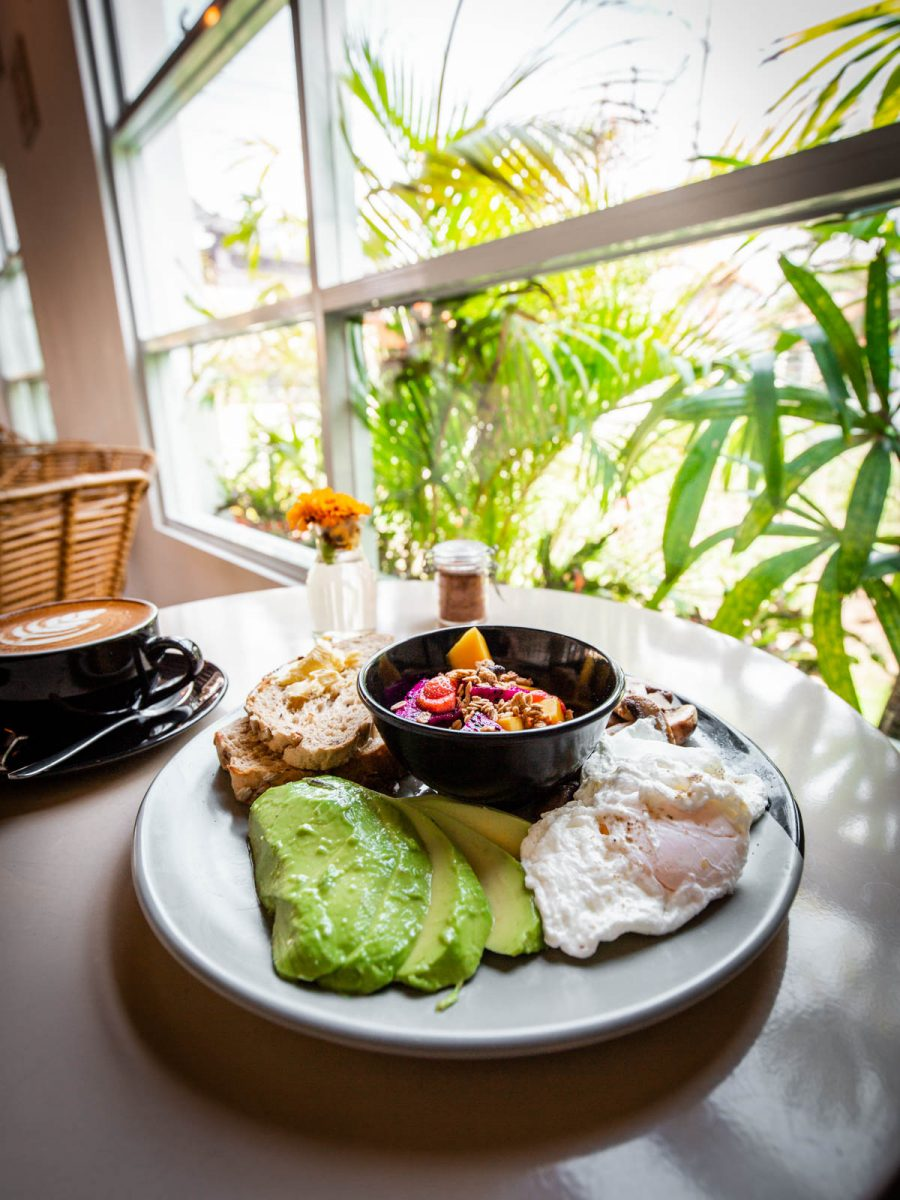 avocado, toast, poached eggs, mushrooms and fruit at magcel cafe canggu