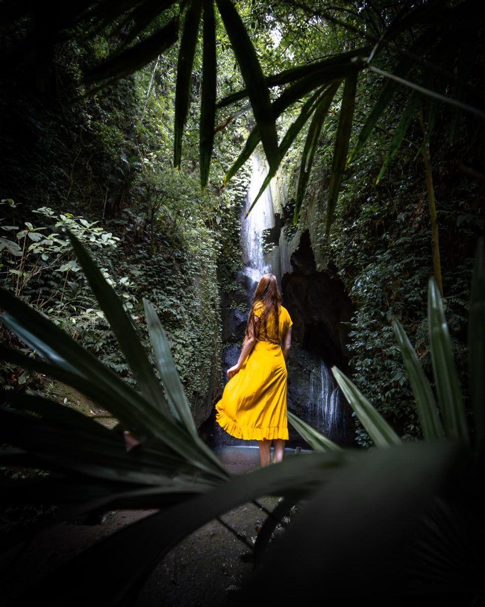 women standing in front of the pengempu waterfall in ubud