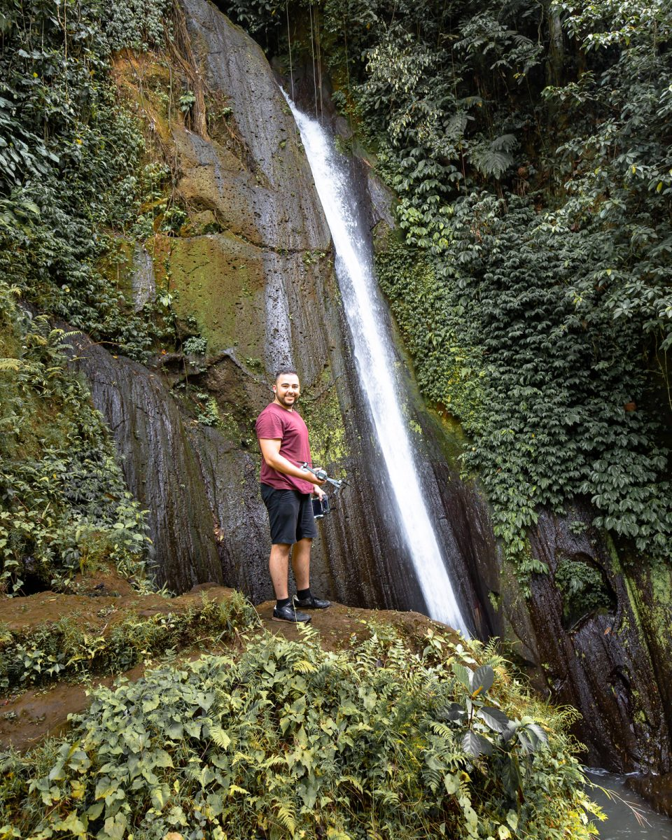 man in front of the dusung kuning waterfall in bali