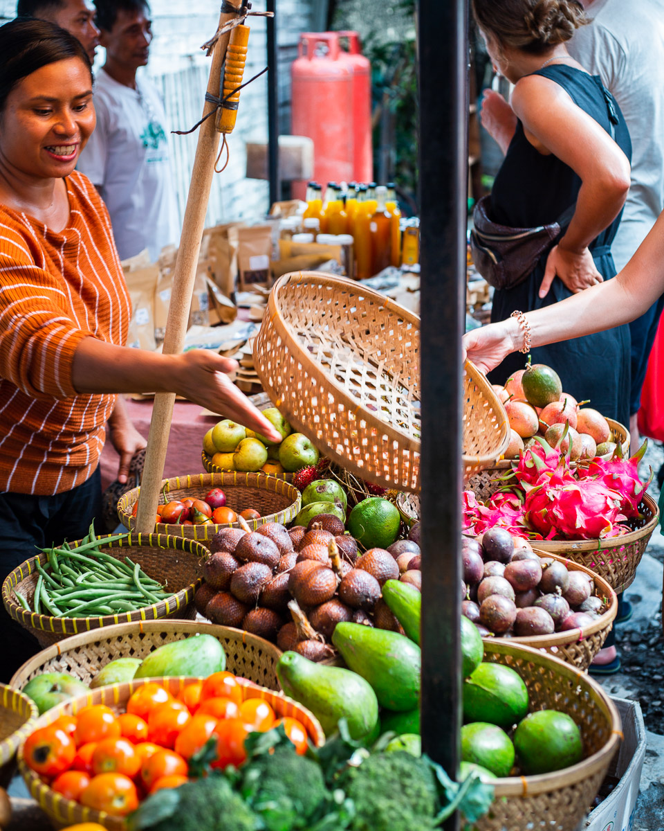support the local economy: woman selling fruits at the samadi sunday market in bali